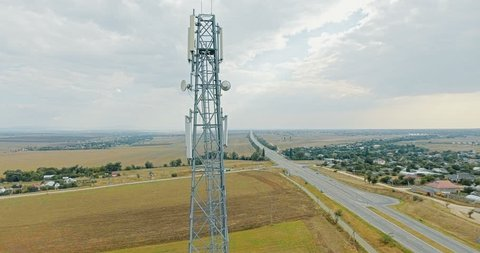 Aerial view on tower of cell phone antenna road with transportation and blue sky. Shoot from drone. 4K video