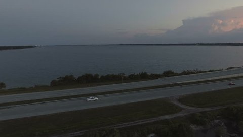 Aerial pan of car driving over Florida inter coastal bridge into the sunset.
