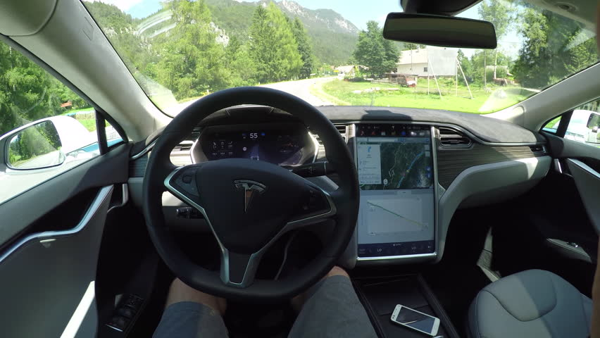 KRANJSKA GORA, SLOVENIA - JULY 17 2016: Unrecognizable person self driving autonomous electric car, navigating and steering without driver on countryside road with overgrown rocky mountains in front