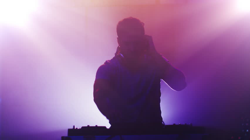 Backlit DJ Playing Music in Nightclub. Silhouette of a DJ. Animation on Background. Shot on RED Cinema Camera in 4K (UHD).