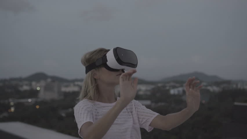Woman having fun with virtual reality glasses while standing on the roof during early evening - 360 video in slow motion | Shutterstock HD Video #19564852