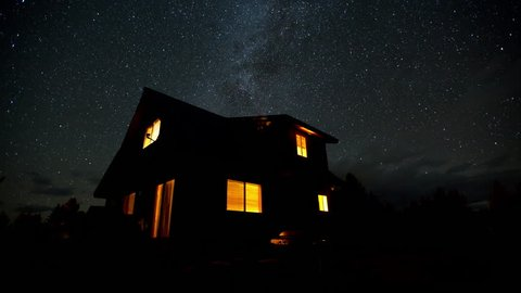 4K time lapse of milky way galaxy stars over a rural cabin house in the woods on a partly cloudy clear calm night in Idaho