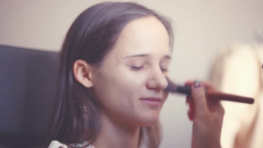 Makeup artist makes a young woman beautiful makeup before an important event. Makeup Applying. 1920x1080 | Shutterstock HD Video #19588429