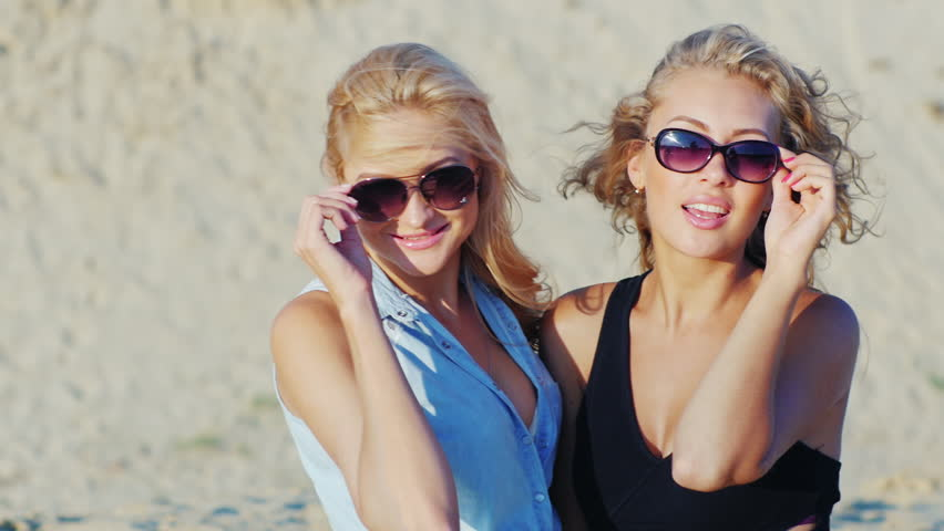 Two young women posing for the camera, smiling. On the beach on a sunny day | Shutterstock HD Video #19631974