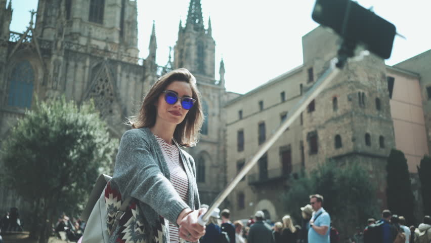 Hipster traveler girl take a selfie portrait on selfie stick with Cathedral, lifestyle travel, slow motion, urban scene, tourism and vacation concept