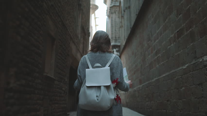 Back view of young hipster traveler girl walking at Barcelona gothic quarter, woman tourist walking with map at Barcelona streets, slow motion, urban scene