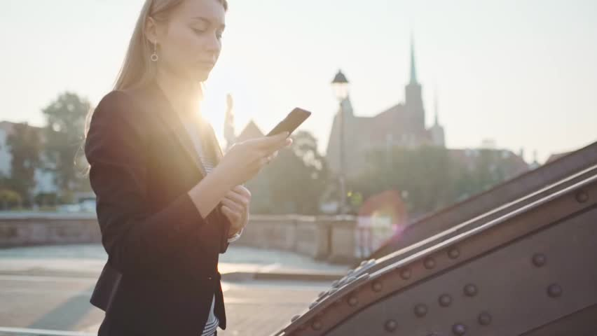 Young Businesswoman Using SmartPhone, Going to Work in the Sunny Morning City. SLOW MOTION. STEADICAM Stabilized Shot. Attractive Professional Business Woman talking on a phone in a city. Lens Flare.