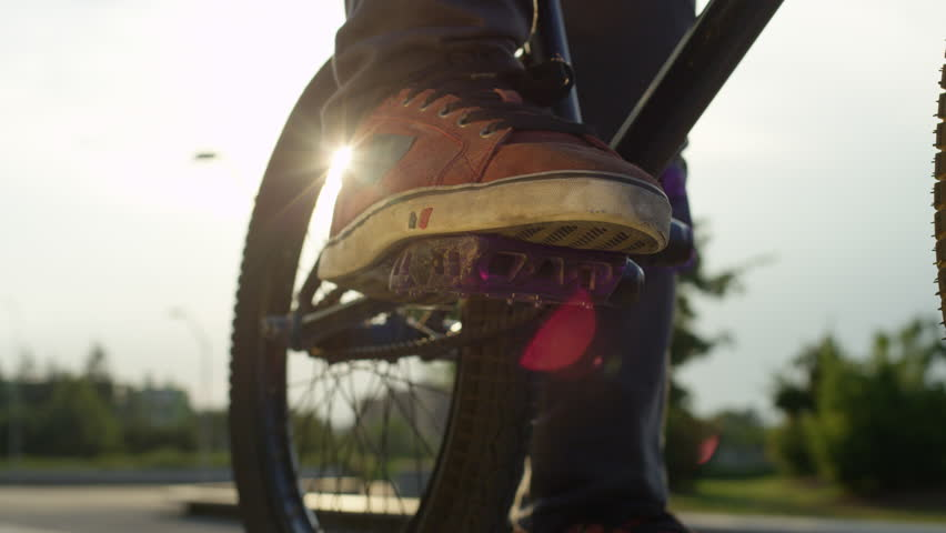 SLOW MOTION CLOSE UP DOF: Extreme bmx biker spinning and placing his foot on a bike pedal on sunny evening. Bmx bike rider playing with pedal and preparing for a bike ride on city street in summer