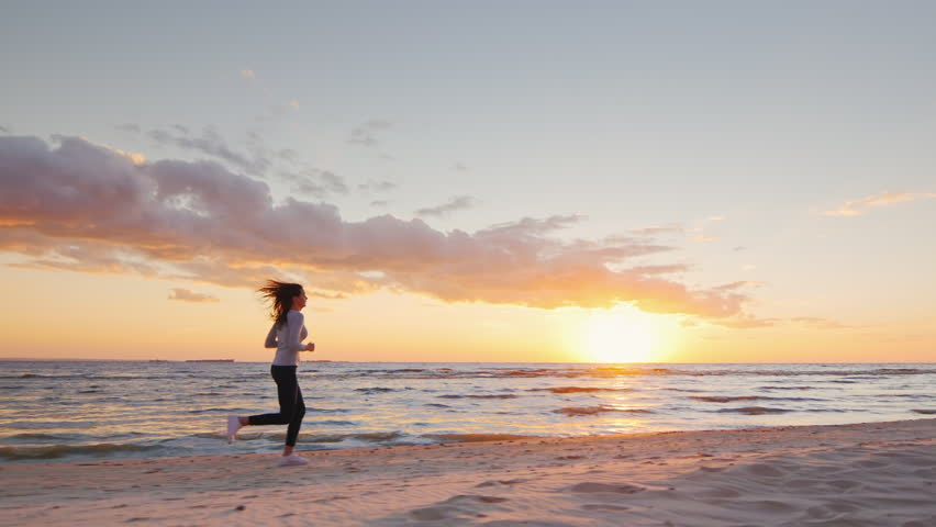 Young attractive woman jogging on the beach at sunset Full length. Beautiful clouds and breathtaking sunset. Steadicam slow motion video.