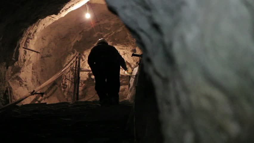 Miner walking inside mine