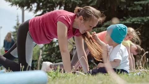 Little baby boy playing with his mother doing knee to elbow plank while training in the park with fitness group