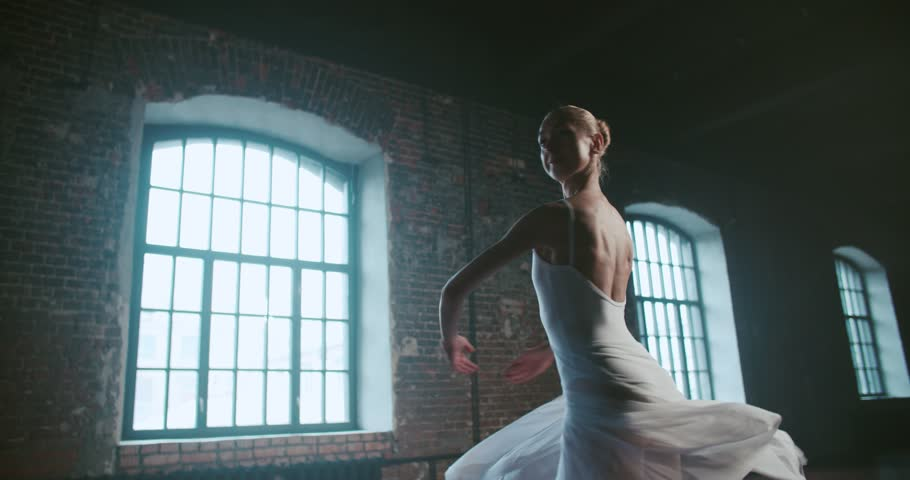 Beautiful girl ballerina performs pirouettes of classical ballet to the loft design Studio,slow motion