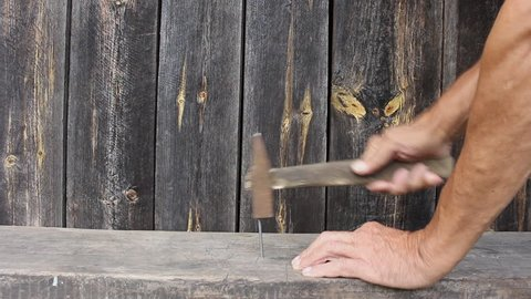 Man hammering nail into Board hammer. Hands of an elderly man, the old hammer a new nail.