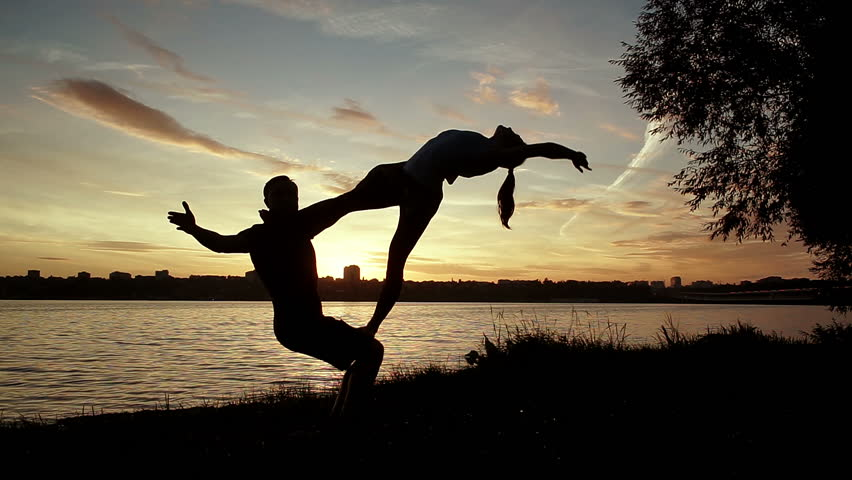Acrobatic yoga on the bank of the river. Young man and woman practicing acrobatic yoga. The dark silhouettes of people in backlight. Wide angle. HD #19759129