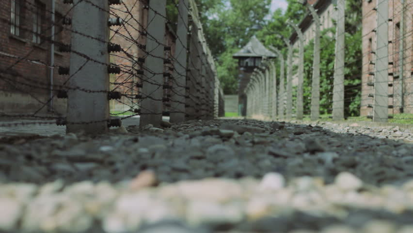 AUSCHWITZ, POLAND - CIRCA 2010: Walkway and barbed wire fence at Auschwitz concentration camp in Poland circa 2010. Dolly move left to right.