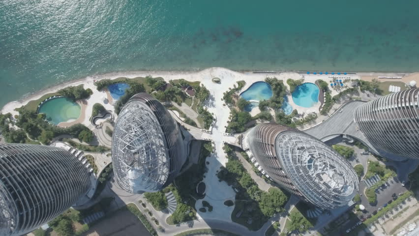 SANYA, CHINA - JULY 2016: Aerial view looking down on the modern Phoenix hotel resort complex on Hainan island in the South China Sea. Rooftops, swimming pools, palm trees.