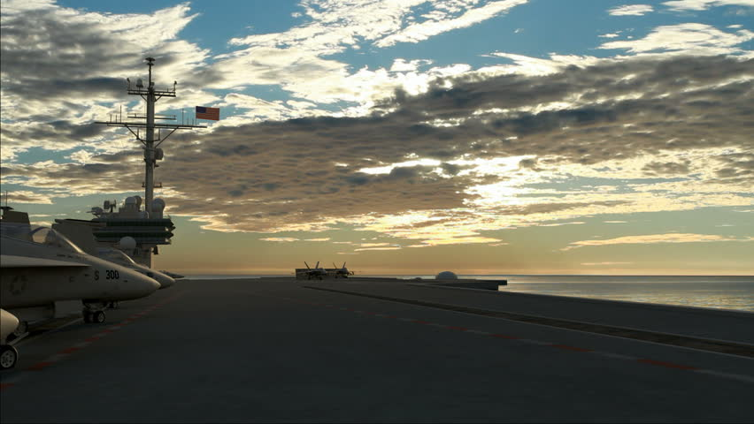 Two F18 Hornets taking off from an American aircraft carrier in the morning.