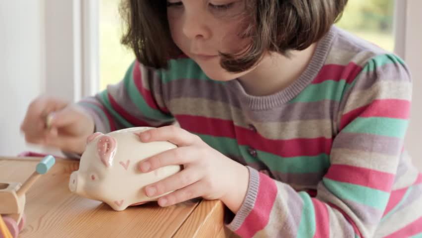 Little girl saving pound coins