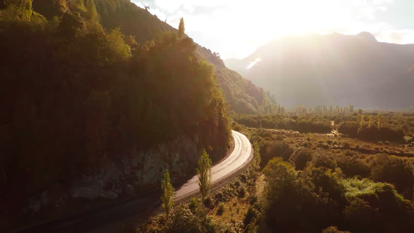 Aerial: Following pickup truck driving next to river in mountains at sunrise 2K