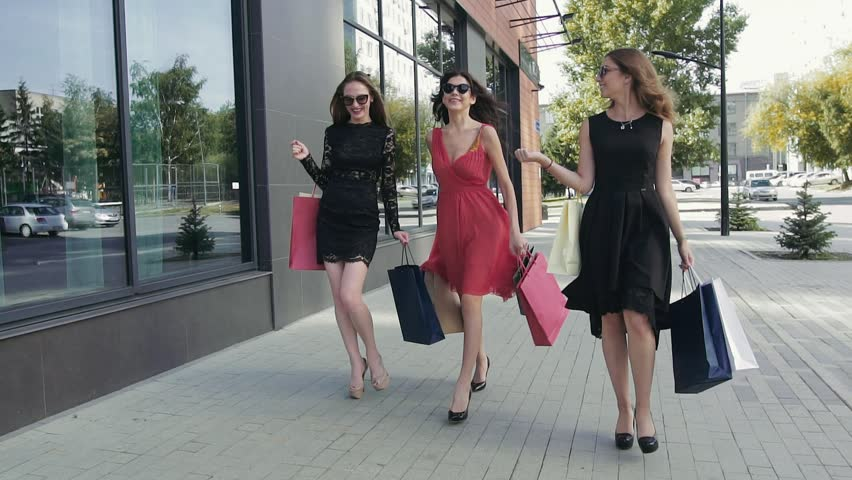 Group of lovely female friends walking down the street after a shopping day | Shutterstock HD Video #19885789