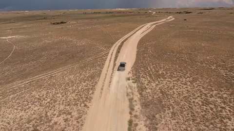 Aerial footage filmed with drone of pickup car riding in desert. Off road SUV car service petroleum in Texas is moving quickly over steppe terrain while is making inspection for safety technology
