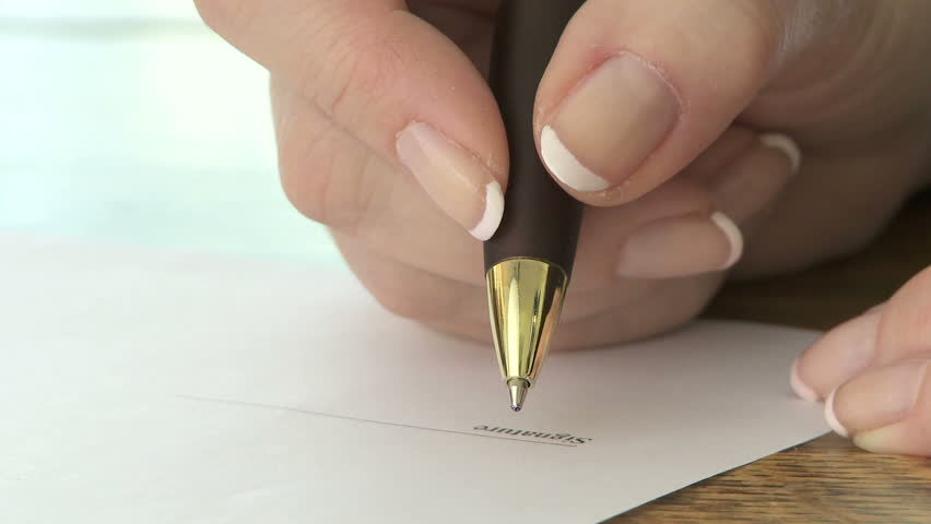 Woman signing signature with a ballpoint pen