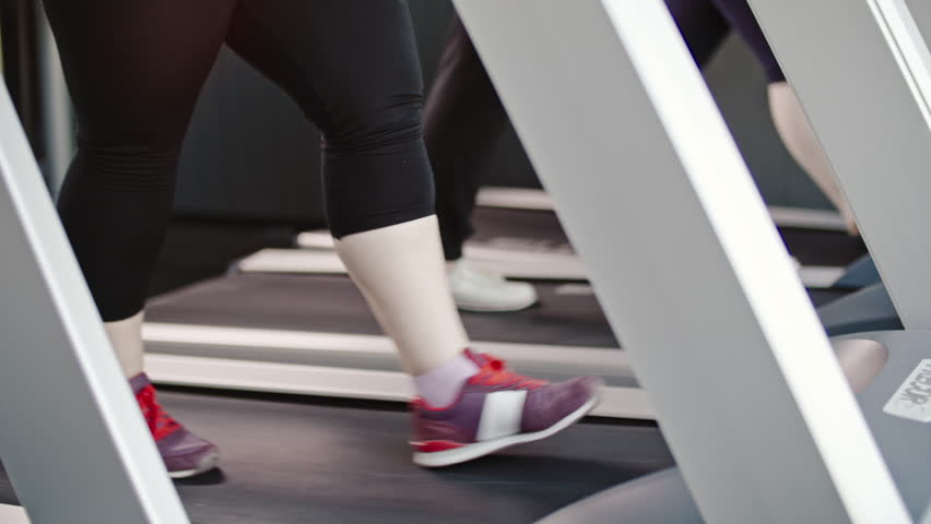 Closeup of legs of overweight women walking on treadmill desk in the gym