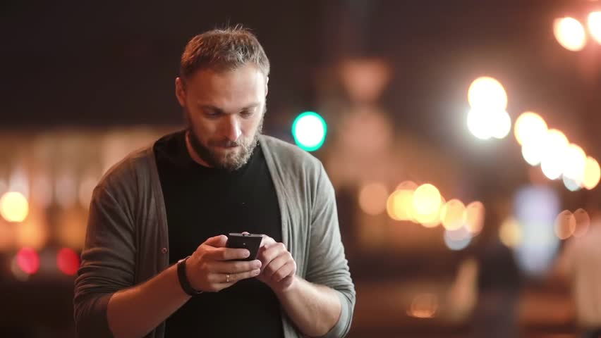 Handsome man texts, uses his smartphone and goes away. Blurred city lights in the street. Modern technology | Shutterstock HD Video #19931812