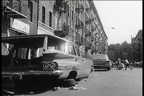 Various angles of apartment blocks in New York City during the 1960s culminate in scenes of children amusing themselves with an open fire hydrant as well as piles of rubbish in the street. (1960s)