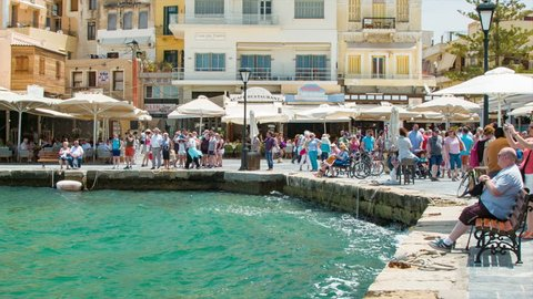 CRETE, GREECE - 2016: Chania Crete Greek Restaurants on Harbor Waterfront with Visiting Tourists Sightseeing an Enjoying the Local Culture on a Sunny Day in Greece