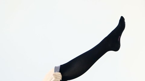 Woman putting on stocking legs, white background