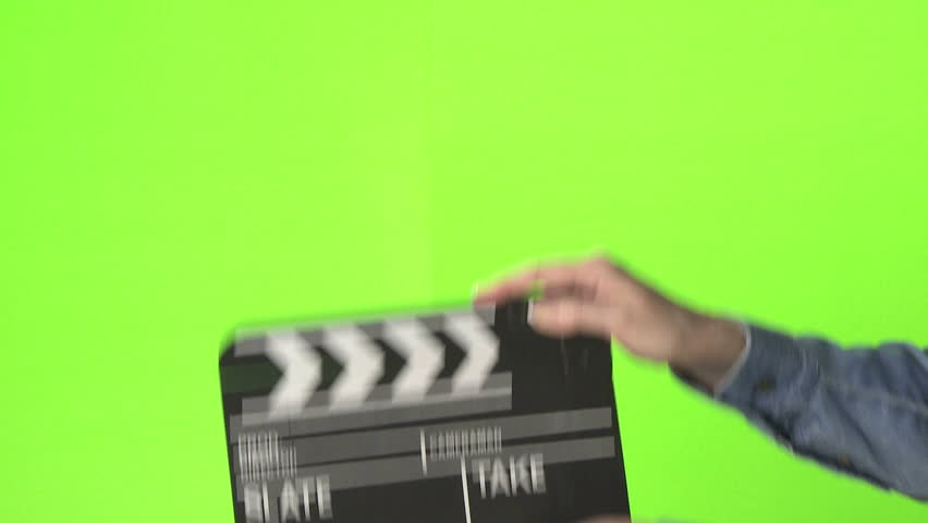 Woman slating a take with clapper board on green screen, medium shot