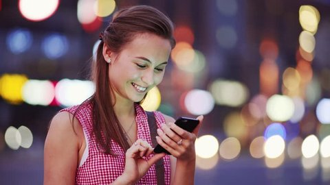 Woman using smart phone at night in city. 4K. Attractive young Woman texting, talking on smartphone outdoors. Tourist Millennial Girl with cellphone, blurred Night Busy Street lights background.