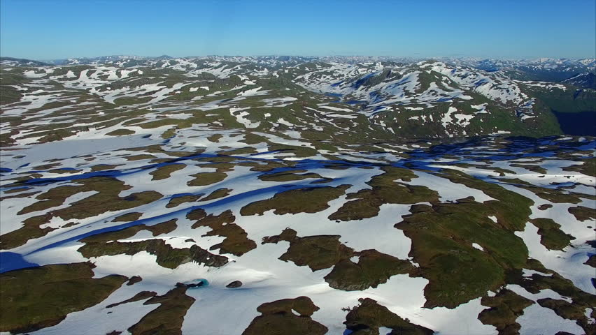 Slow flight above cold landscape covered with patches of snow and ice on sunny summer day. Norway, Myrkdalen area. Aerial 4k Ultra HD. | Shutterstock HD Video #19978738
