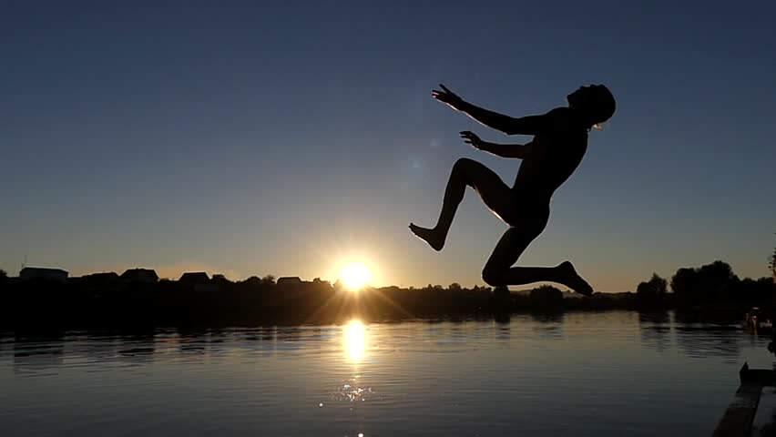 the Guy Jumps Into the Water Back Flips. Fail in Slow Motion. the Action at Sunset.