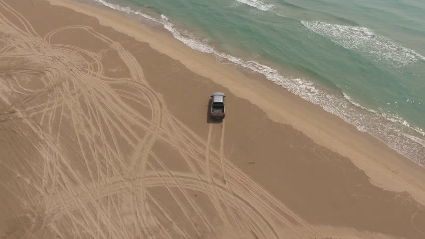Aerial footage filmed on flying drone camera with traveler in a car stopped at the beach to admire the incredible beauty of the sea during road trip journey. The concept of freedom in travel #20034709