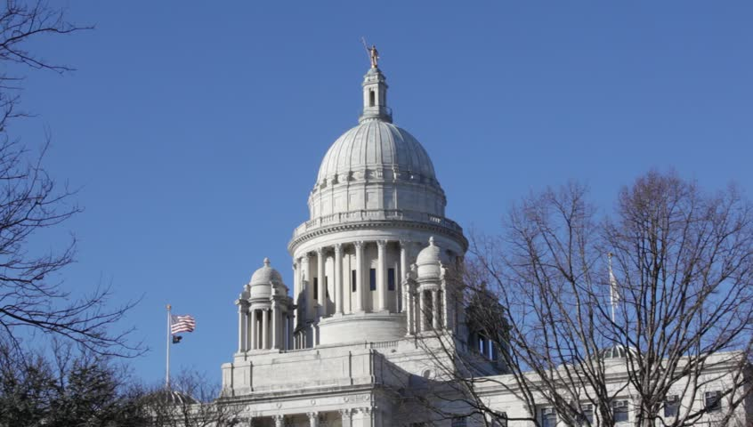 Providence Rhode Island State Capital building close up of the dome with American flags flying on clear day with blue sky. 1080 p HD 30 sec