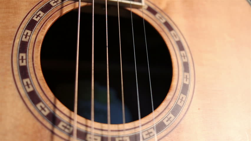 Dolly shot of close up view of acoustic guitar