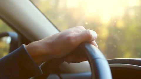 Man driving his car. Driving car at holiday, nature. Male Hand on steering wheel closeup