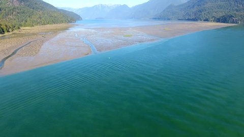 Aerial view of  a large sand bar in Pitt River. Pitt Lake and the Coast Mountains are seen in the background. Pitt River is located in Pitt Meadows, British Columbia, Canada.