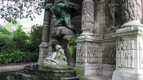 Pigeons play and take bath at Medici Fountain at Jardin Des Luxembourg in Paris