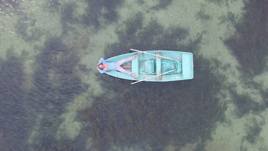 Aerial view. Man is relaxing in a small boat, drifting in the sea. Concept - alone in the ocean. #20090872