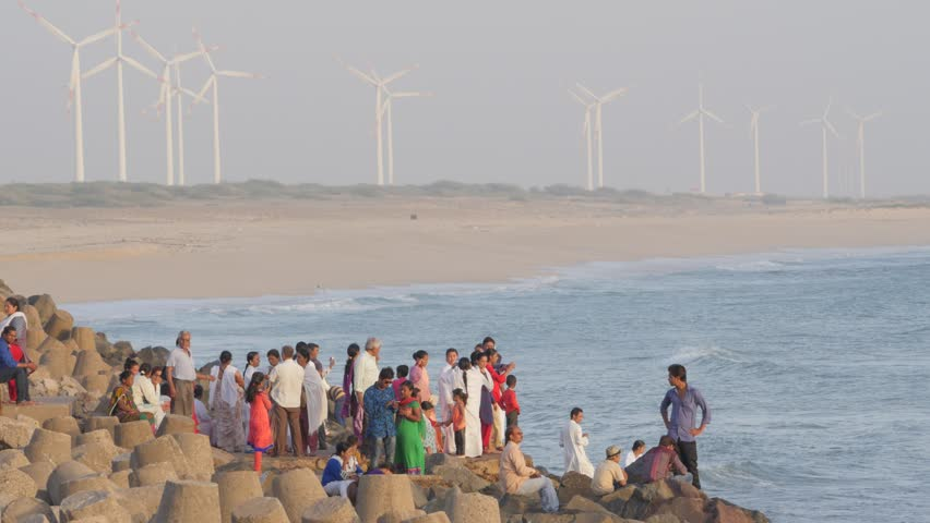 Dwarka,India - March 27,2016: People on rocky coast with windmills