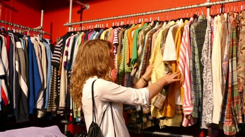 Paris, France: Short clip (to exclude logos from shot) of a pretty young woman looking through a line of shirts hanging in a vintage clothes shop.