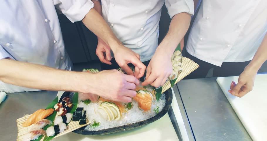 Restaurant Kitchen Hand 4k video shooting: three professional chefs prepare sushi set in a