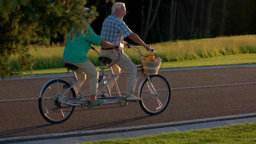 Senior couple riding tandem bicycle. Two people on a bike. Follow the sun. Picking up speed.