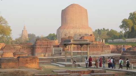 Sarnath,India - February 25,2016: Pilgrims walking around monastery ruins with Dhamekh Stupa