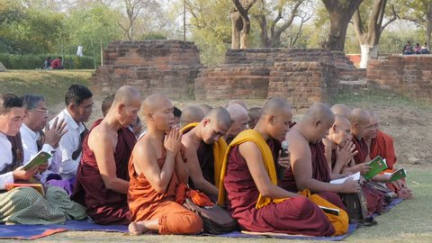 Sarnath,India - February 25,2016: Monks praing at monastery ruins around Dhamekh Stupa