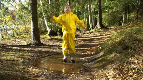Little girl in a yellow rubber suit is jumping in a puddle.