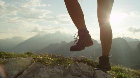 SLOW MOTION, CLOSE UP: Courageous female hiker climbing mountaintop, walking off trail on dangerous rough rocky mountain ridge. Steep wall opening beautiful view on high European Alps sunbathing